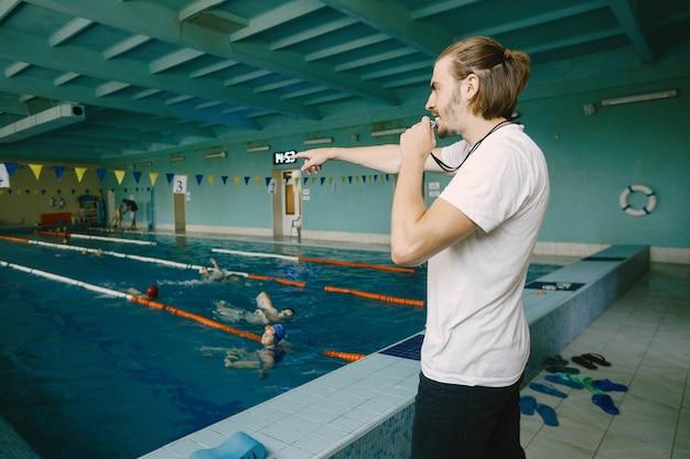 Männlicher schwimmtrainer, der am swimmingpool steht. er zeigt gerade hand, um den schüler zu korrigieren. schwimmtechnik, professionell.