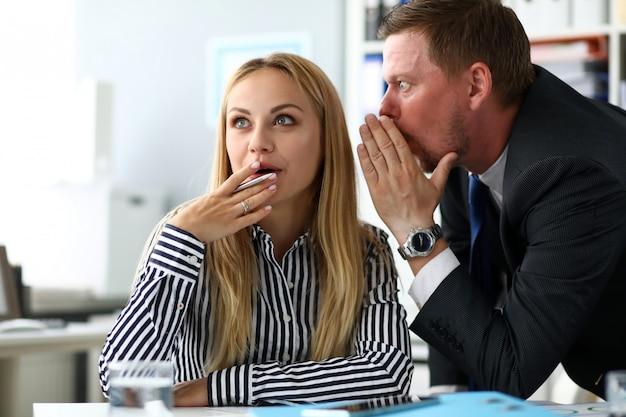 Männlicher sekretär, der etwas geheimes wissen mit weiblichem kollegen teilt
