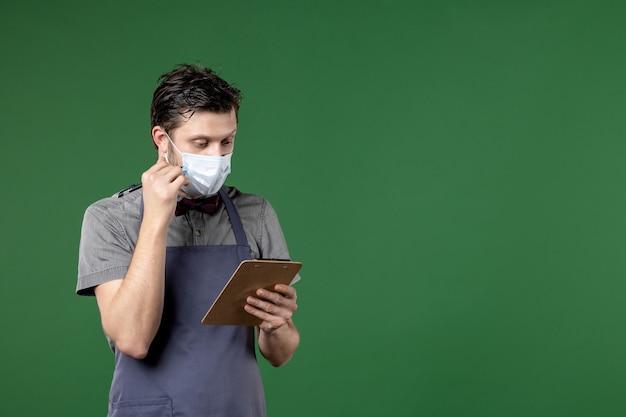 Männlicher server in uniform mit medizinischer maske und konzentriert auf scheckbuchstift auf grünem hintergrund