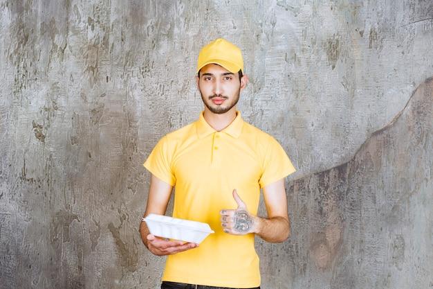 Männlicher servicemitarbeiter in gelber uniform, der eine weiße box zum mitnehmen hält und ein genusszeichen zeigt