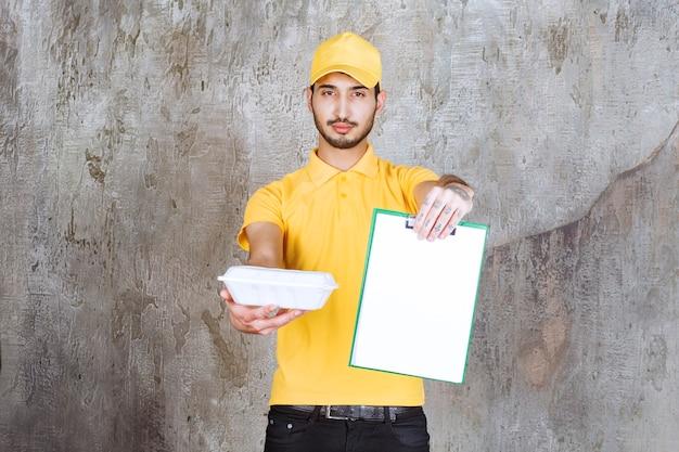 Männlicher servicemitarbeiter in gelber uniform, der eine weiße box zum mitnehmen hält und um unterschrift bittet.