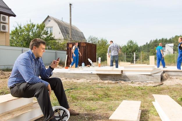 Männlicher site engineer beschäftigte nachrichten mit seinem mobiltelefon im projektbereich.