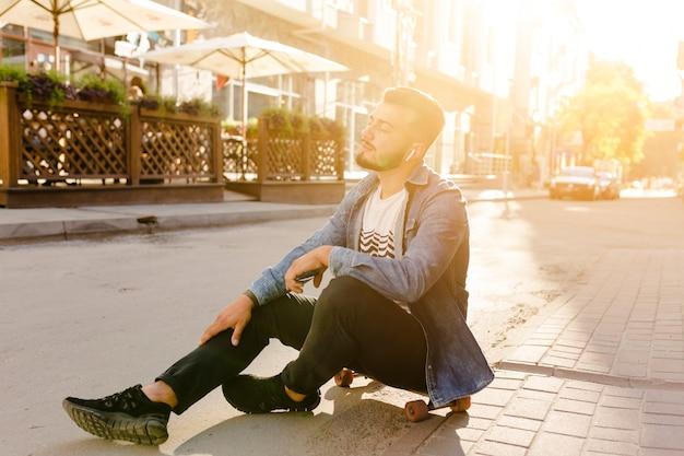 Männlicher skateboardfahrer, der auf dem skateboard hört musik sitzt