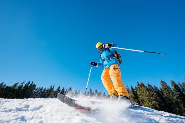 Männlicher skifahrer, der auf neuschnee ski fährt