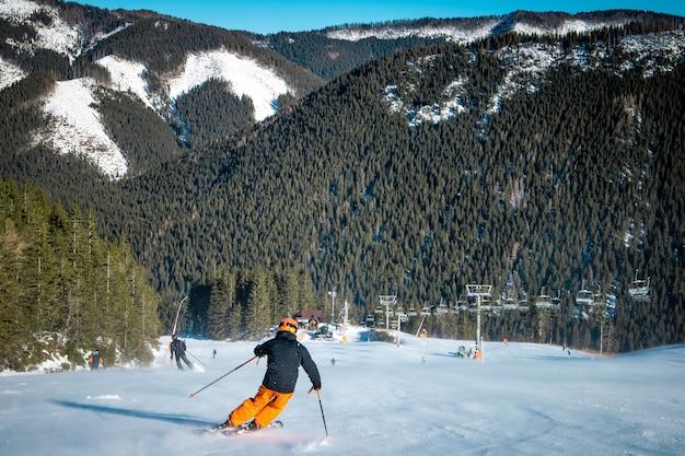 Männlicher skifahrer, der den hang an einem sonnigen tag schnitzt