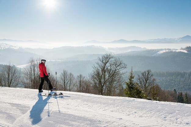 Männlicher skifahrer, der nach der fahrt steht, die oben auf der skipiste steht und sich umschaut, die atemberaubende aussicht auf schneebedeckte berge an einem sonnigen wintertag genießt.