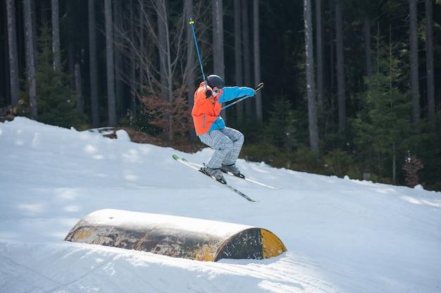 Männlicher skifahrer, der über hürde mit wald von tannen fliegt