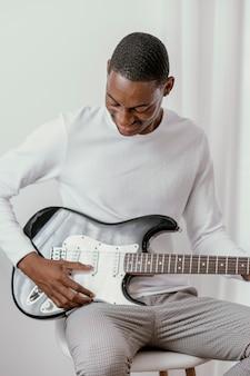 Männlicher smiley-musiker, der e-gitarre spielt