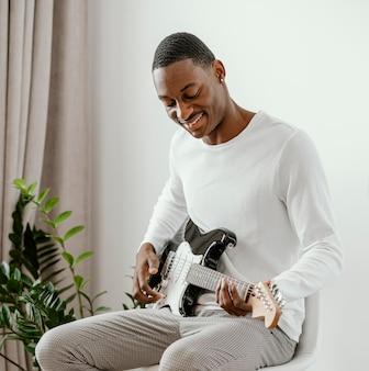 Männlicher smiley-musiker, der zu hause e-gitarre spielt