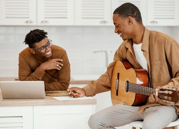 Männlicher smiley-musiker zu hause auf stuhl, der gitarre spielt und laptop verwendet