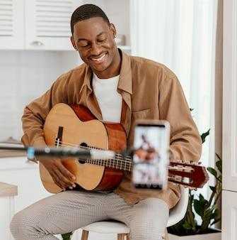 Männlicher smiley-musiker zu hause auf stuhl, der gitarre spielt und mit smartphone aufnimmt