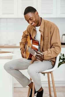 Männlicher smiley-musiker zu hause auf stuhl, der gitarre spielt