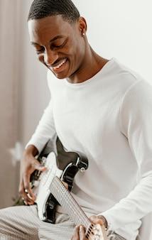 Männlicher smiley-musiker zu hause, der e-gitarre spielt