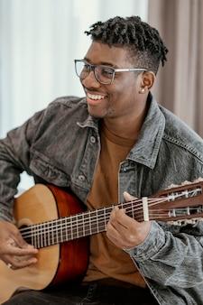 Männlicher smiley-musiker zu hause, der gitarre spielt