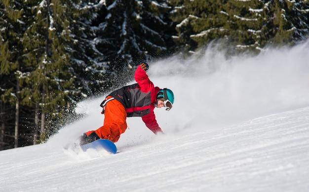Männlicher snowboarder, der auf schneebedecktem hang reitet