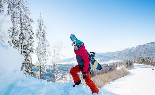 Männlicher snowboarder, der sein brett trägt, das in den bergen am sonnigen wintertag geht