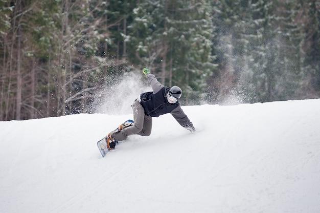 Männlicher snowboarder, der über die steigung am wintertag springt