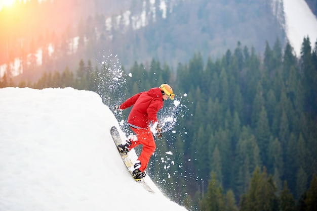 Männlicher snowboarder, der von der spitze des schneebedeckten abhangs mit snowboard reitet.