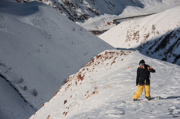 Männlicher snowboarder des freerides, der auf der bergspitze steht