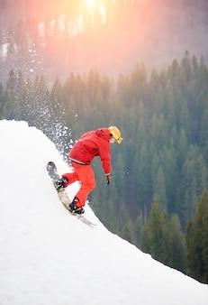Männlicher snowboarder freerider in einem roten klagenreiten von der spitze des schneebedeckten hügels mit snowboard