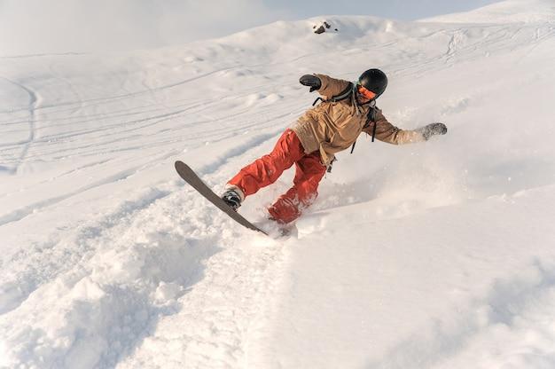 Männlicher snowboarder in der sportkleidung und im sturzhelm, die hinunter den pulverschneehügel reiten