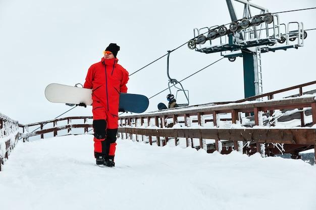Männlicher snowboarder in einem roten anzug, der auf dem verschneiten hügel mit snowboard-, ski- und snowboardkonzept spaziert.