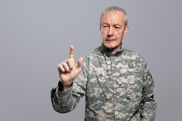 Männlicher soldat, der den zeigefinger auf einem unsichtbaren bildschirm drückt