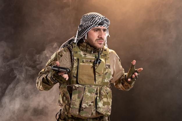 Männlicher soldat in militäruniform mit pistole auf dunkler rauchiger wand