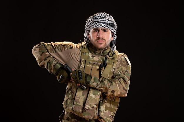 Männlicher soldat in tarnung, der mit gewehr auf schwarzer wand kämpft