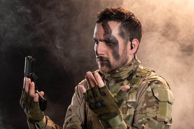 Männlicher soldat in tarnung, der sich auf rauchiger dunkler wand ergibt