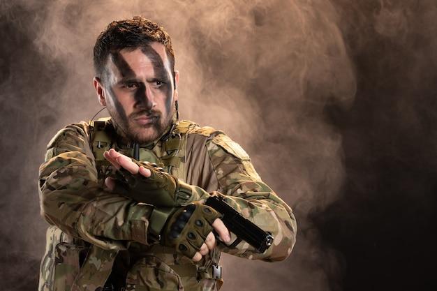 Männlicher soldat in tarnung mit gewehr auf dunkler rauchiger wand