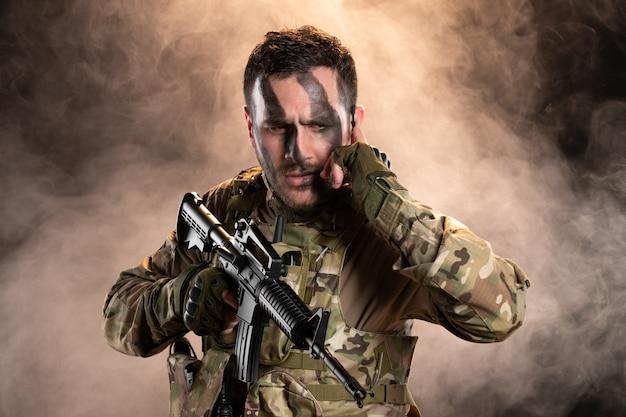 Männlicher soldat in tarnung mit maschinengewehr auf der dunklen rauchigen wand