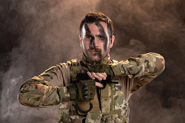 Männlicher soldat in tarnung nachladende waffe auf rauchiger dunkler wand