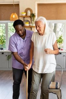 Männlicher sozialarbeiter, der sich um eine alte frau kümmert