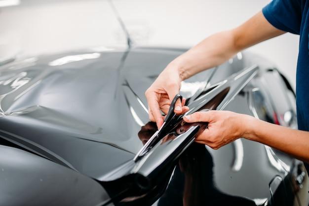 Männlicher spezialist mit schere, autotönungsfolien-installationsprozess, getöntes autoglas-installationsverfahren