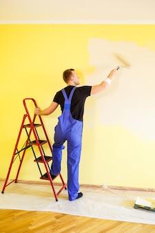 Männlicher spezialist streicht die wand mit farbe im innenbereich, reparaturkonzept