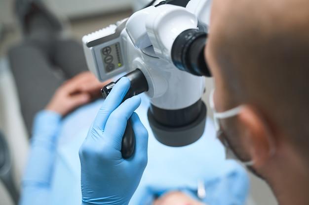 Männlicher spezialist verwendet digitale geräte zur untersuchung der zähne und untersucht das mikroskop zur diagnose