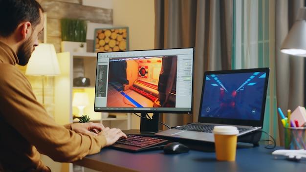 Männlicher spieleentwickler, der auf der tastatur tippt, während er ein neues level des spiels entwickelt.