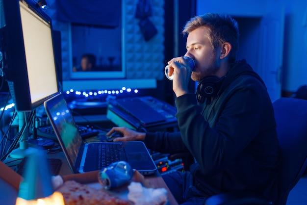 Männlicher spieler, der einen energiegetränk an seinem arbeitsplatz mit laptop und desktop-pc trinkt, spieleabendlebensstil. computerspielspieler in seinem zimmer mit neonlicht, streamer