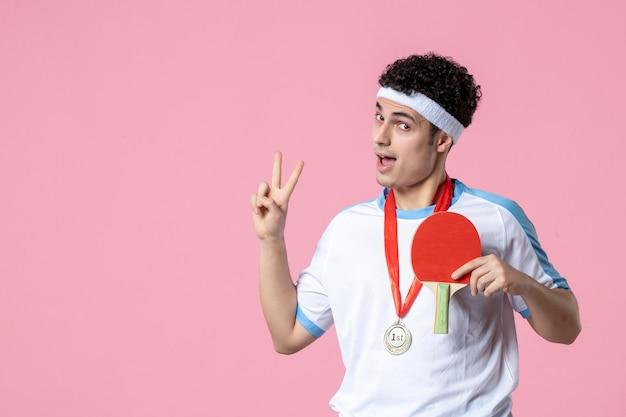 Männlicher spieler der vorderansicht mit kleinem schläger und medaille