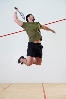 Männlicher spieler springt, um während eines squash-matches einen ball zu schlagen
