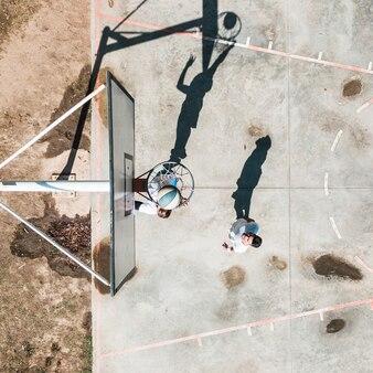 Männlicher spieler zwei, der mit ball am gericht draußen übt