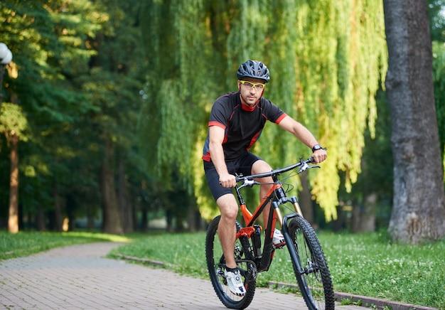 Männlicher sportler, der auf fahrrad im freien radelt