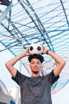 Männlicher sportler, der fußball über kopf gegen metallstruktur hält
