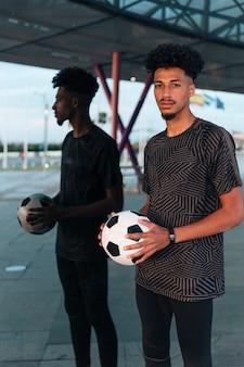 Männlicher sportler, der mit fußball auf widergespiegeltem hintergrund steht