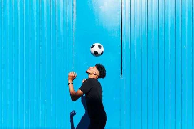 Männlicher sportler, der mit fußball gegen cyan-blaue wand trainiert