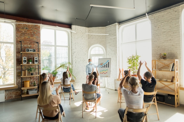 Männlicher sprecher, der präsentation im saal des universitätsworkshops gibt. publikum oder konferenzsaal