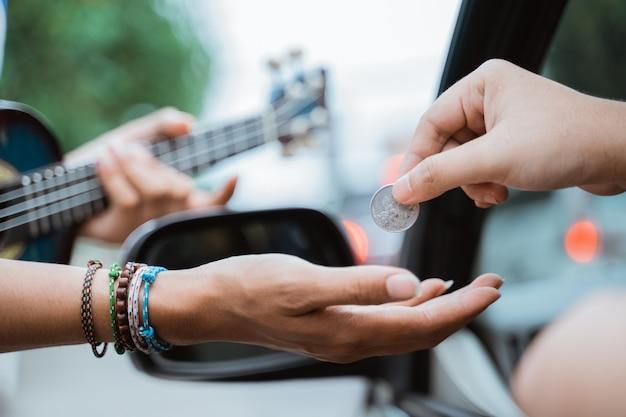 Männlicher straßenmusiker bettelt an der ampel um geld
