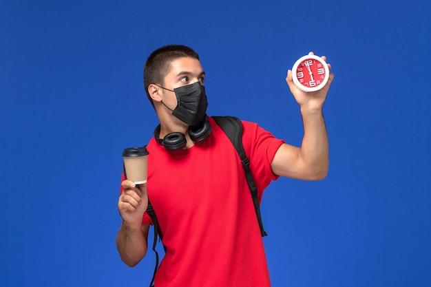 Männlicher student der vorderansicht im roten t-shirt, das maske mit rucksack hält, der uhrenkaffee auf blauem schreibtisch hält.