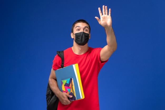 Männlicher student der vorderansicht im roten t-shirt, das rucksack in der schwarzen sterilen maske hält, die das heft hält und dateien, die auf blauem hintergrund winken.